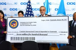 CICIG Commissioner Iván Velásquez holds the ceremonial check from the US embassy in Guatemala, with Ambassador Todd Robinson on the right. (US Embassy)